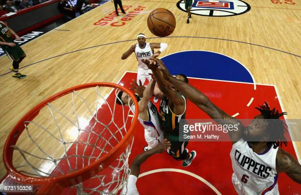 DeAndre Jordan and JJ Redick of the Los Angeles Clippers defend against a shot by Derrick Favors of the Utah Jazz during the first half of Game Five...