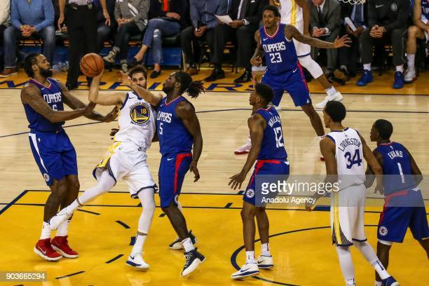 DeAndre Jordan and Montrezl Harrell of LA Clippers in action against Omri Casspi of Golden State Warriors during the NBA basketball game between LA...