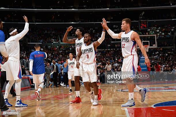 DeAndre Jordan Chris Paul and Blake Griffin of the Los Angeles Clippers celebrate against the Denver Nuggets during a preseason game on October 2...