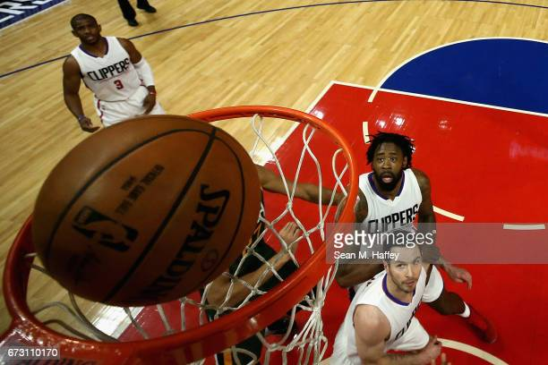 DeAndre Jordan Chris Paul and JJ Redick of the Los Angeles Clippers look on after Rudy Gobert of the Utah Jazz makes a shot during the first half of...