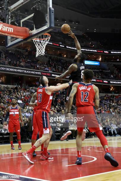DeAndre Jordan of the LA Clippers puts up a shot in front of Marcin Gortat and Kelly Oubre Jr #12 of the Washington Wizards in the first half at...