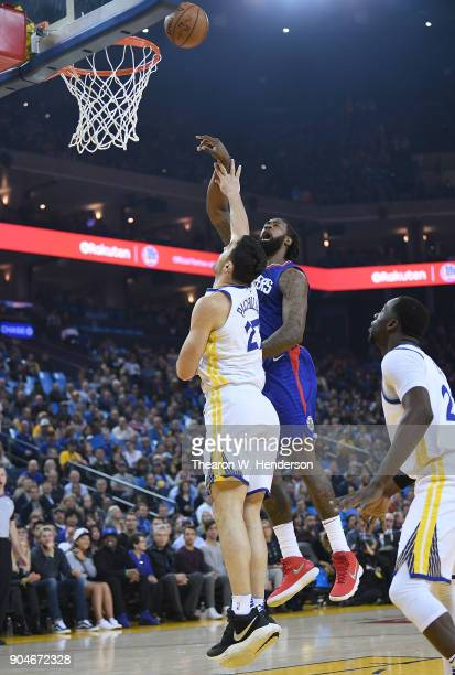 DeAndre Jordan of the LA Clippers shoots over Zaza Pachulia of the Golden State Warriors during the first half of their NBA Basketball game at ORACLE...