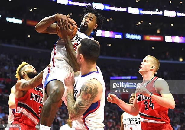 DeAndre Jordan of the Los Angeles Clippers grabs a rebound from Allen Crabbe and Mason Plumlee of the Portland Trail Blazers during the first quarter...