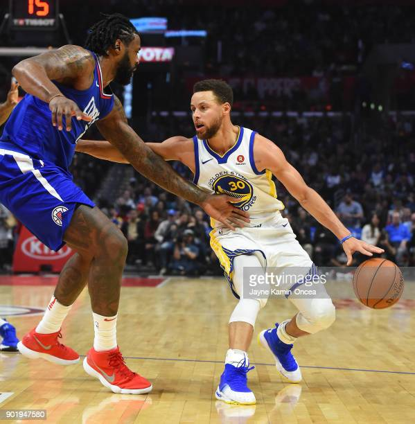DeAndre Jordan of the Los Angeles Clippers guards Stephen Curry of the Golden State Warriors as he drives to the basket in the second half of the...