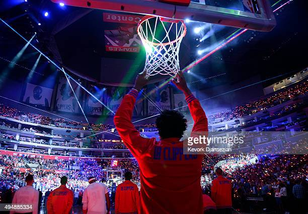 DeAndre Jordan of the Los Angeles Clippers hangs on to the net during pre game ceremonies before their home opener against the Dallas Mavericks at...