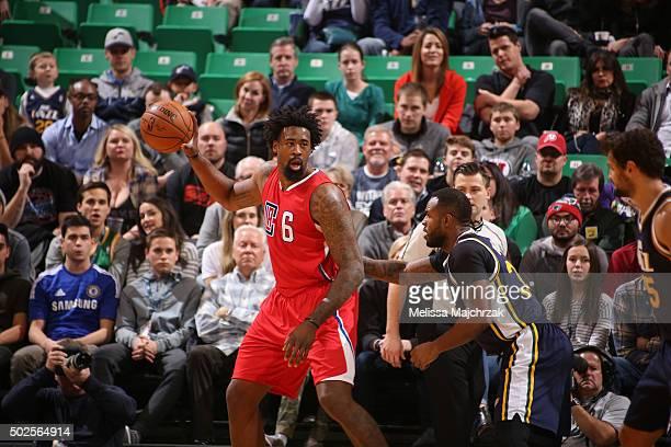 DeAndre Jordan of the Los Angeles Clippers posts up against Trevor Booker of the Utah Jazz on December 26 2015 at vivintSmartHome Arena in Salt Lake...