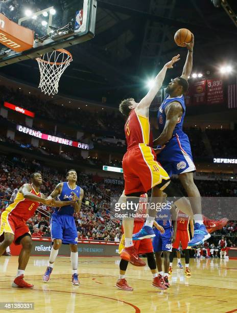 DeAndre Jordan of the Los Angeles Clippers shoots over Omer Asik of the Houston Rockets during the game at the Toyota Center on March 29 2014 in...