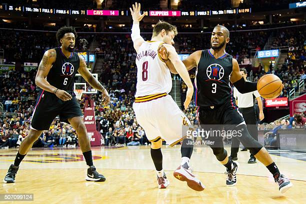 DeAndre Jordan of the Los Angeles Clippers watches as Matthew Dellavedova of the Cleveland Cavaliers guards Chris Paul during the first half at...