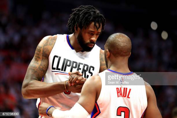 DeAndre Jordan talks with Chris Paul of the Los Angeles Clippers during the second half of Game Seven of the Western Conference Quarterfinals against...