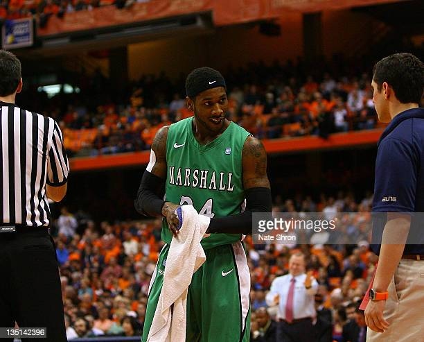 DeAndre Kane of the Marshall Thundering Herd wipes beer off his hands after falling into the crowd during a play against the Syracuse Orange during...