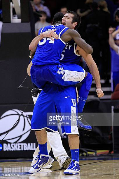 DeAndre Liggins celebrates with Josh Harrellson of the Kentucky Wildcats after defeating the Ohio State Buckeyes in the east regional semifinal of...