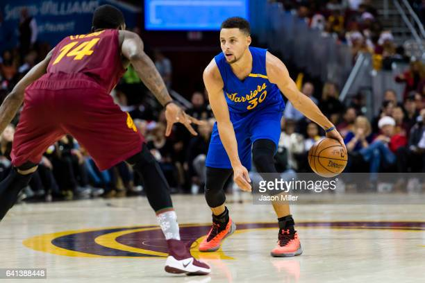 DeAndre Liggins of the Cleveland Cavaliers guards Stephen Curry of the Golden State Warriors during the first half at Quicken Loans Arena on December...