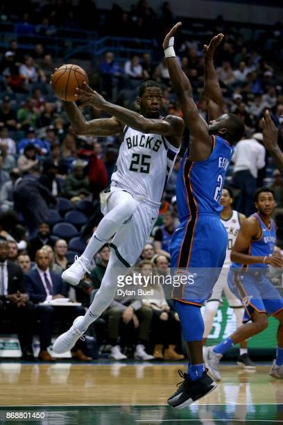 DeAndre Liggins of the Milwaukee Bucks dribbles the ball while being guarded by Raymond Felton of the Oklahoma City Thunder in the fourth quarter at...