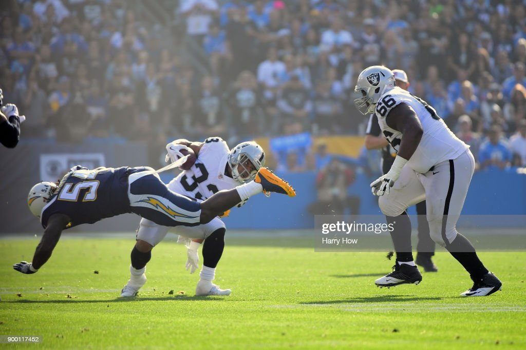 DeAndre Washington #33 of the Oakland Raiders avoids the tackle by Melvin Ingram #54 of the Los Angeles Chargers during the first quarter of the game at StubHub Center on December 31, 2017 in Carson, California.