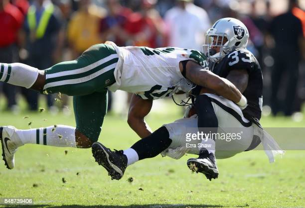 DeAndre Washington of the Oakland Raiders is tackled by Darron Lee of the New York Jets at OaklandAlameda County Coliseum on September 17 2017 in...