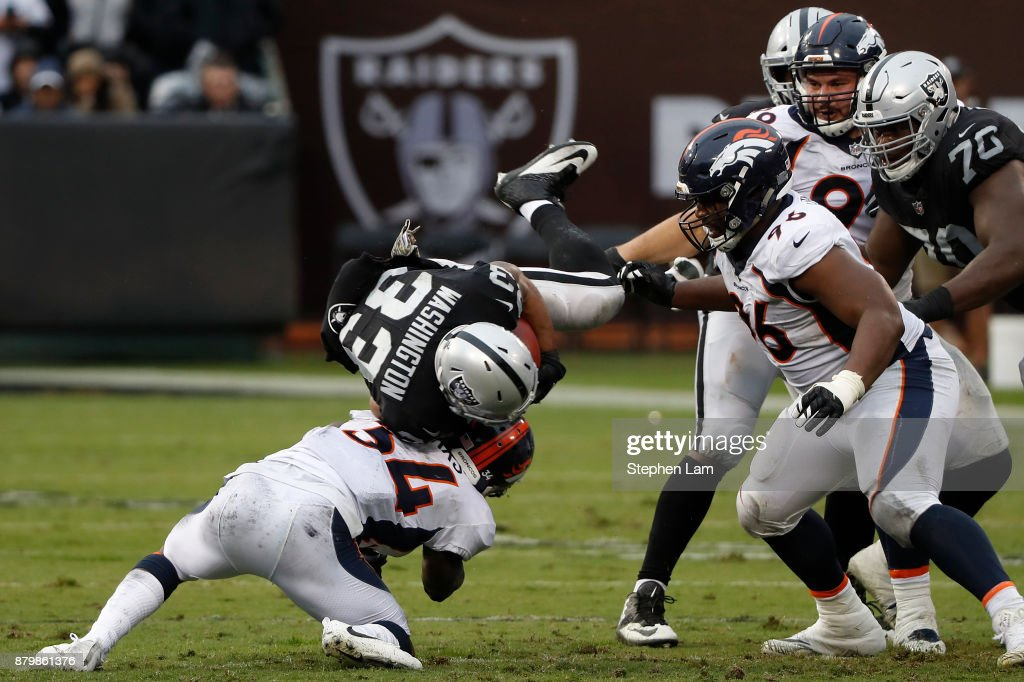 DeAndre Washington #33 of the Oakland Raiders is tackled by Will Parks of the Denver Broncos during the second quarter of their NFL football game against the Denver Broncos at Oakland-Alameda County Coliseum on November 26, 2017 in Oakland, California.