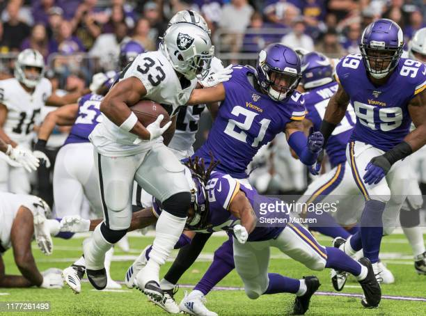 DeAndre Washington of the Oakland Raiders runs with the ball as he's pursued by Minnesota Vikings defenders at US Bank Stadium on September 22 2019...
