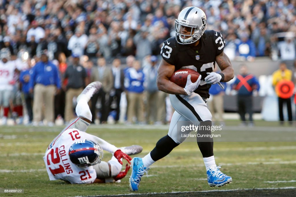 DeAndre Washington #33 of the Oakland Raiders scores on a nine-yard run against the New York Giants during their NFL game at Oakland-Alameda County Coliseum on December 3, 2017 in Oakland, California.