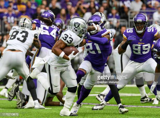 DeAndre Washington of the Oakland Raiders stiff arms Mike Hughes of the Minnesota Vikings in the first quarter of the game at US Bank Stadium on...