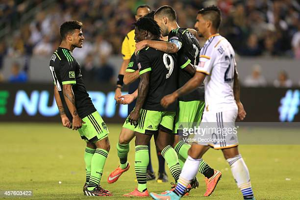 DeAndre Yedlin and Clint Dempsey of Seattle Sounders FC congratulate jubilant teammate Obafemi Martins after Martins scored a goal to tie the match...