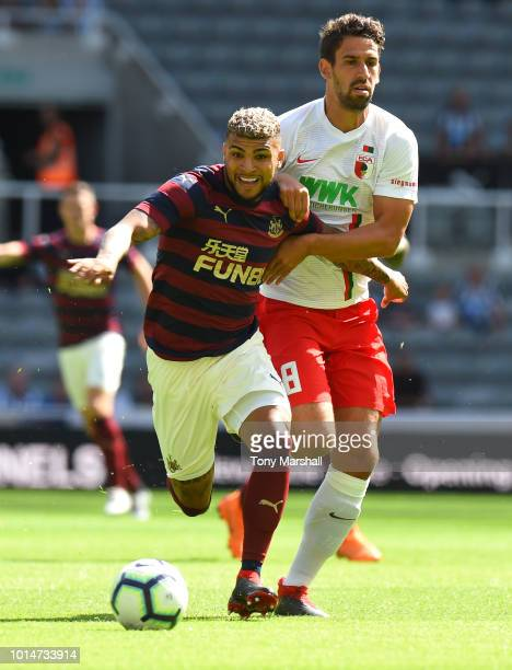 DeAndre Yedlin of Newcastle United is tackled by Rani Khedira of FC Augsburg during the PreSeason Friendly match between Newcastle United and FC...