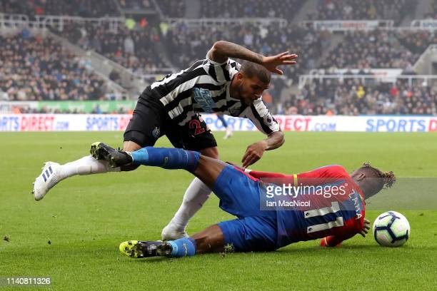 Deandre Yedlin of Newcastle United is tackled by Wilfried Zaha of Crystal Palace during the Premier League match between Newcastle United and Crystal...
