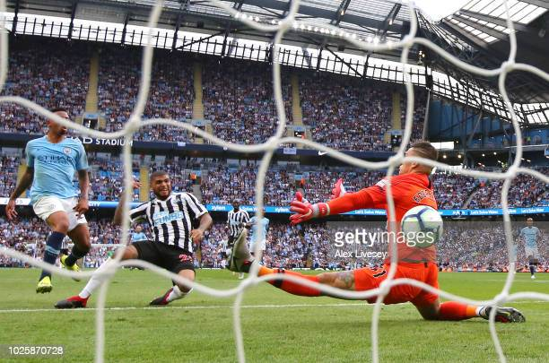 Deandre Yedlin of Newcastle United scores his team's first goal past Ederson of Manchester City during the Premier League match between Manchester...
