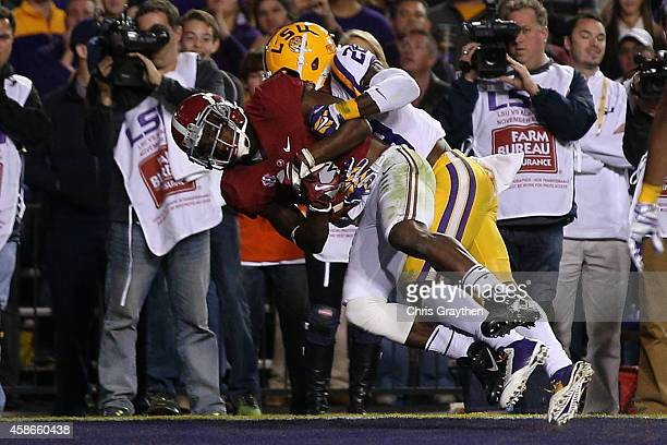 DeAndrew White of the Alabama Crimson Tide catches a touchdown pass in overtime as he is tackled by Jalen Mills of the LSU Tigers at Tiger Stadium on...