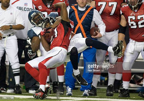 DeAngelo Hall of the Atlanta Falcons is dragged out of bounds by Courtney Taylor of the Seattle Seahawks at Georgia Dome on December 30, 2007 in...