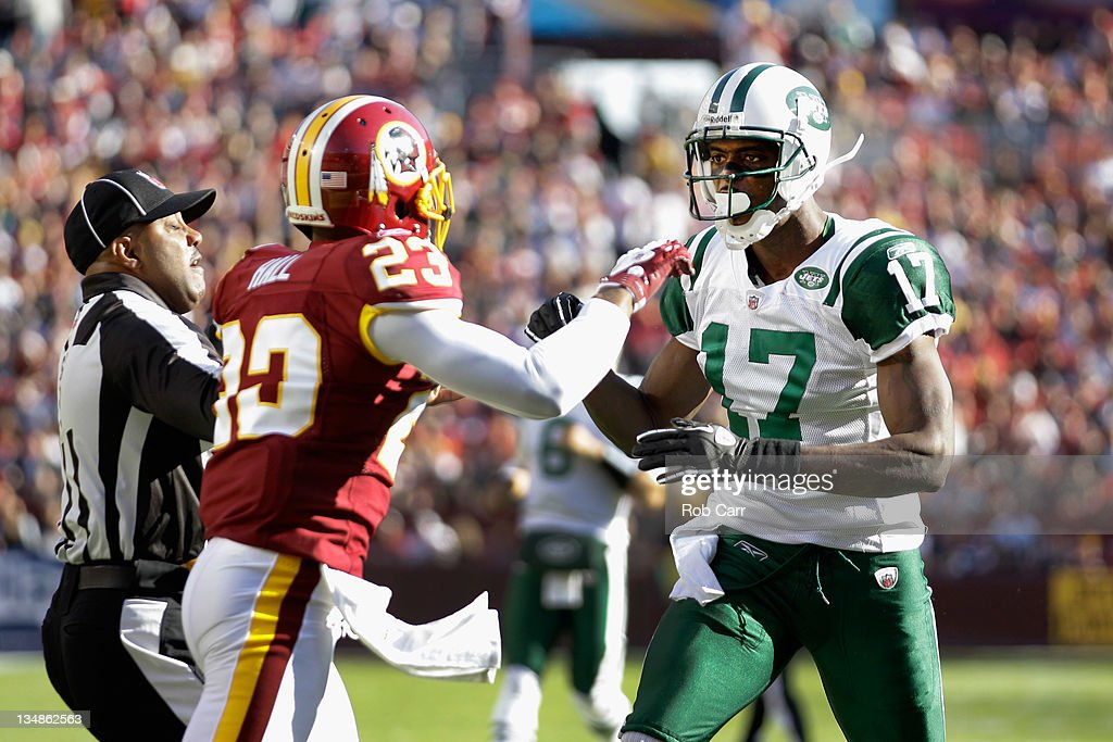 DeAngelo Hall #23 of the Washington Redskins and Plaxico Burress #17 of the New York Jets exchange words during the first half at FedExField on December 4, 2011 in Landover, Maryland.