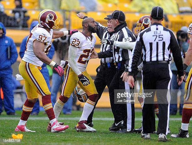 DeAngelo Hall of the Washington Redskins is held back by Lorenzo Alexander of the Washington Redskins after being ejected from the game for arguing...