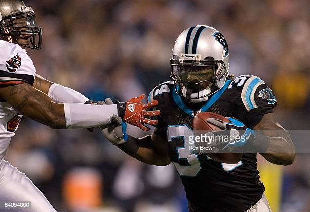DeAngelo Williams of the Carolina Panthers fights off the tackle of Quincy Black of the Tampa Bay Buccaneers during the first half on December 8 2008...