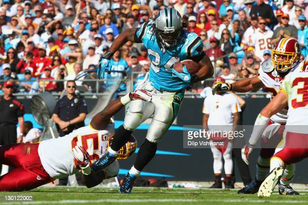 DeAngelo Williams of the Carolina Panthers slips out of a tackle by London Fletcher of the Washington Redskins at the Bank of America Stadium on...