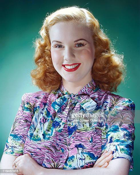 Deanna Durbin Canadian actress and singer smiling and wearing a shortsleeved patterned blouse in a studio portrait against a green background circa...