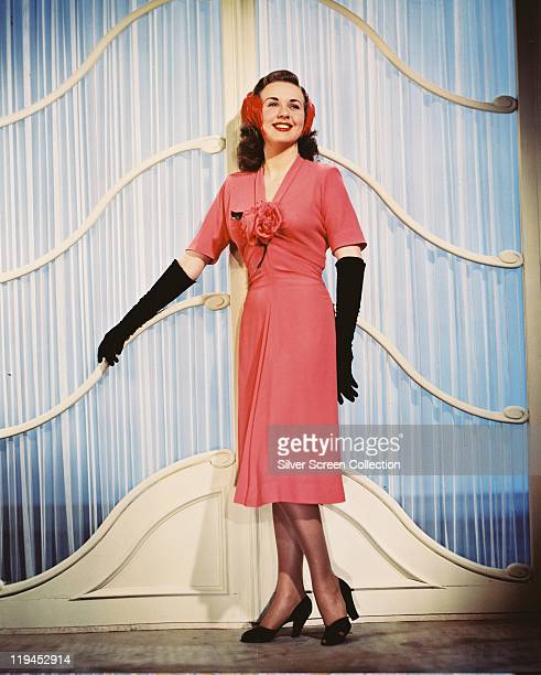 Deanna Durbin Canadian actress and singer smiling and wearing a shortsleeved pink dress with long black gloves circa 1955