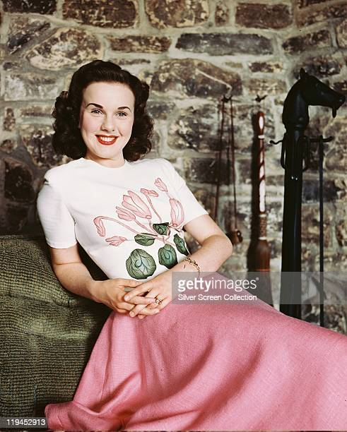 Deanna Durbin Canadian actress and singer smiling and wearing a white shortsleeved top with a floral motif and a pink skirt in a studio portrait...