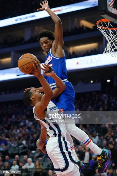 De'Anthony Melton of the Memphis Grizzlies commits an offensive foul against De'Aaron Fox of the Sacramento Kings during the first half at Golden 1...