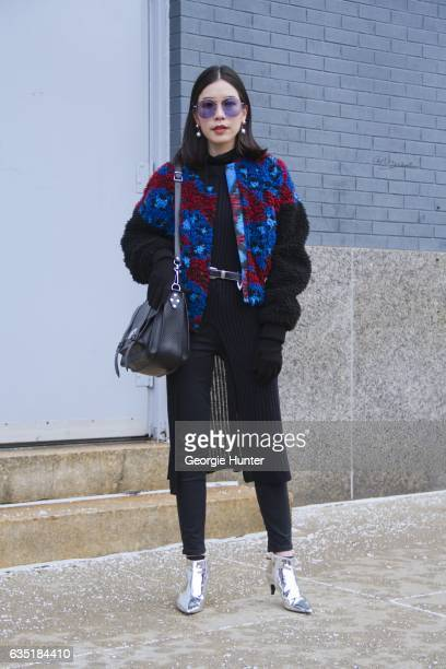 Dear Pichamon is seen at Spring Studios outside the Phillip Lim show wearing faux fur blue and red bomber jacket with black sleeves black leather bag...