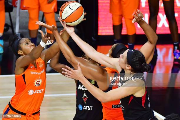 Dearica Hamby of the Las Vegas Aces shoots the ball with pressure from Briann January and Brionna Jones of the Connecticut Sun during the second half...
