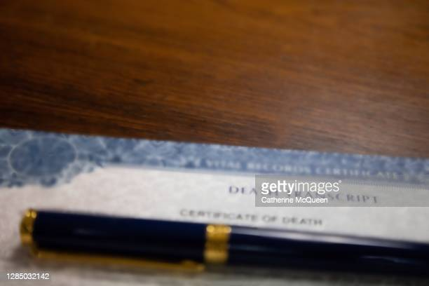 death certificate on wooden desk under pen - centers for disease control and prevention stock pictures, royalty-free photos & images