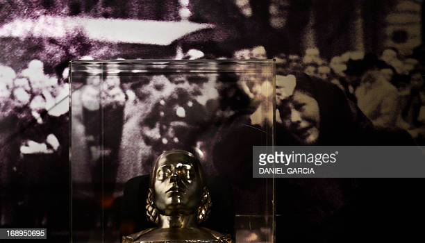 A death mask made in 1952 by Argentine silversmith Carlos Pallarols Cuni of Eva Duarte de Peron Evita and a oicture of her funeral displayed at the...