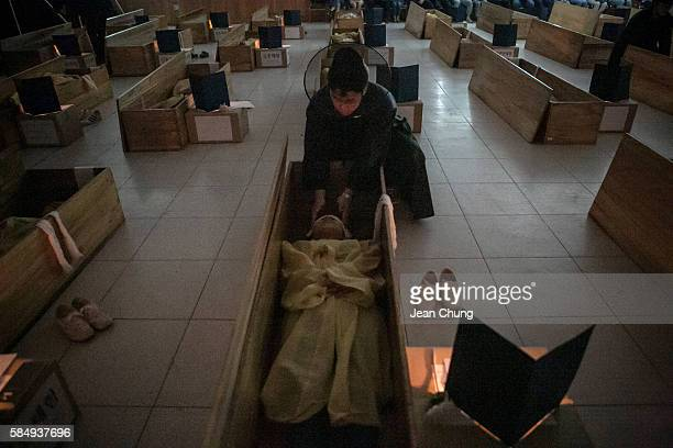 A death master wearing a black robe hides the eyes and tie up the wrists of the participants during a Death Experience/Fake Funeral session held by...