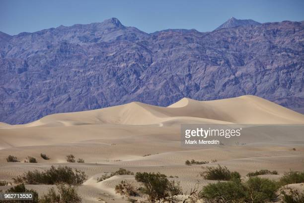 Death Valley landscape of sand dunes and rocky mountain range