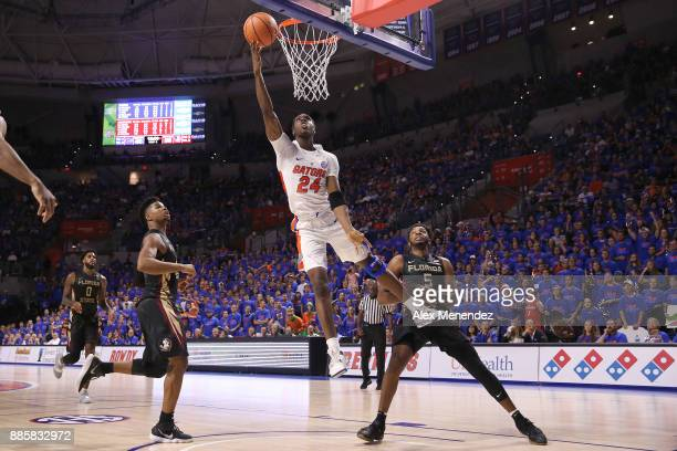 Deaundrae Ballard of the Florida Gators drives to the net past PJ Savoy of the Florida State Seminoles during a NCAA basketball game at the Stephen C...