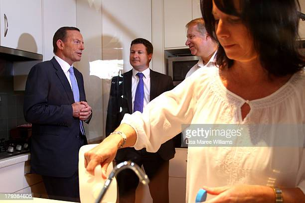 Deb Schmusch makes a coffee for Australian Opposition Leader Tony Abbott whilst he speaks with her husband Eric on September 3 2013 in Adelaide...