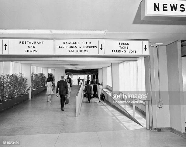 Debarking passengers proceeding to the baggage pickup at LaGuardia Airport in Queens New York New York July 1964