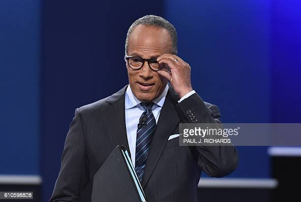 Debate moderator Lester Holt adjusts his glasses during the first presidential debate at Hofstra University in Hempstead New York on September 26...