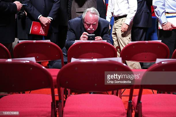 Debate spectator take photos with a smartphone of first lady Michelle Obama's chair prior to the Presidential Debate at the University of Denver on...