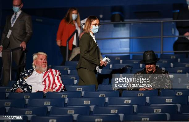 A debate worker walks towards US professional golfer John Daly and musician Kid Rock providing them with a facemask to wear ahead of the final...