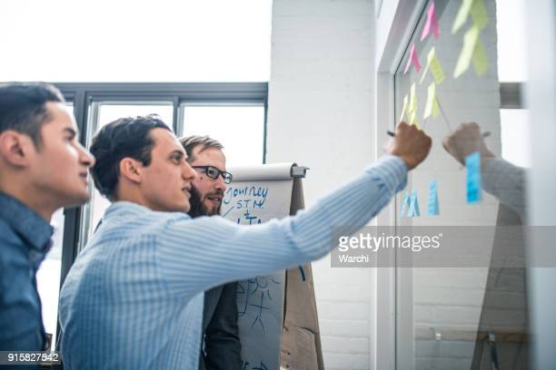 debating business ideas with post-it notes on the window - diagramma di flusso foto e immagini stock